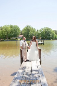 bride and groom looking at one another on pier at combsberry inn