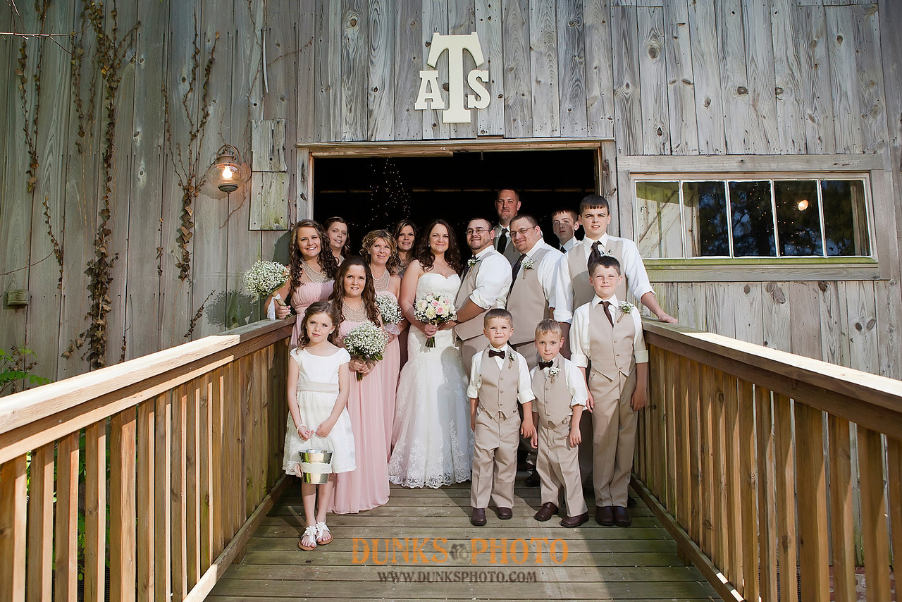 wedding party posed for picture in front of rustic barn