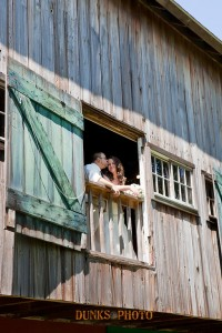 married couple posing through barn window