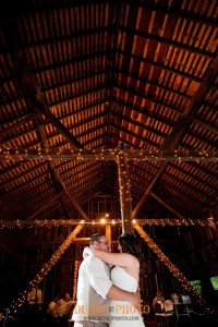 couple dancing in barn decorated with white lights on beams