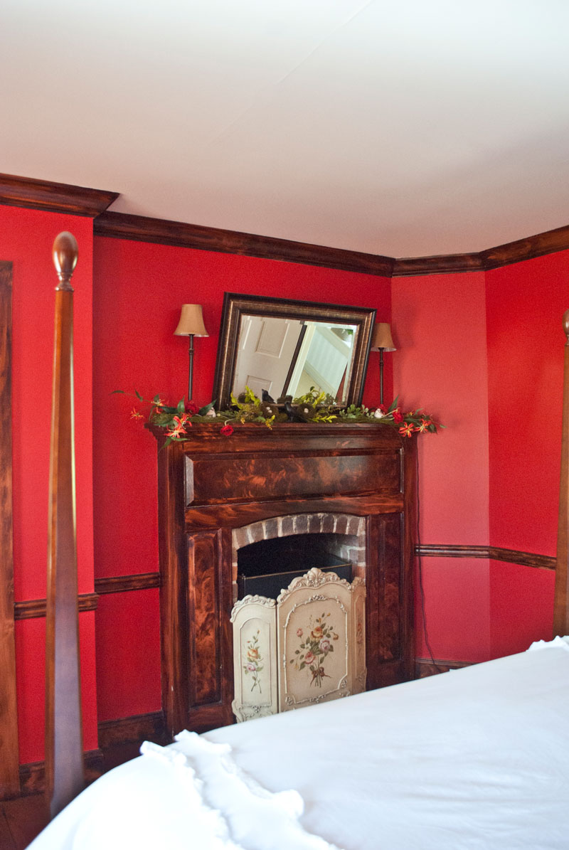 Combsberry Inn Waterfront bedroom with fireplace and red painted walls