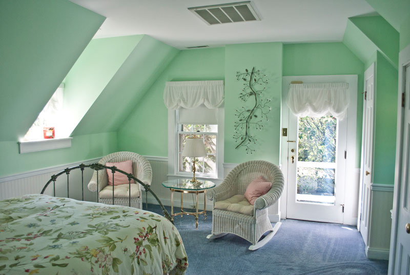 mint green walls in combsberry inn victorian room with white wicker rockers by door