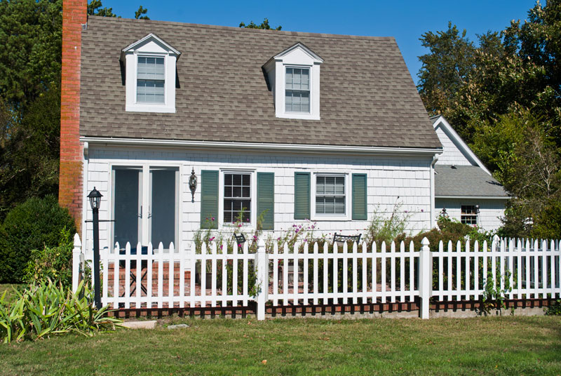 white cottage with green shutters and picket fence at comsberry inn