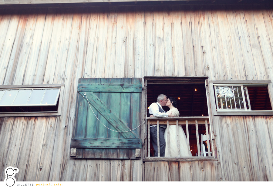 just married couple kissing standing by barn window