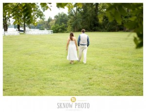 bride and groom walking towards white chairs set up for wedding ceremony