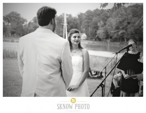 black and white photo of bride and groom during ceremony by water
