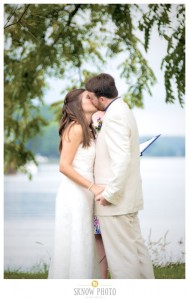 bride and groom kissing by water at combsberry inn
