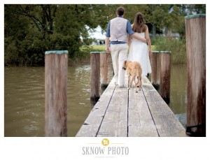 couple standing back to on pier with dog behind them
