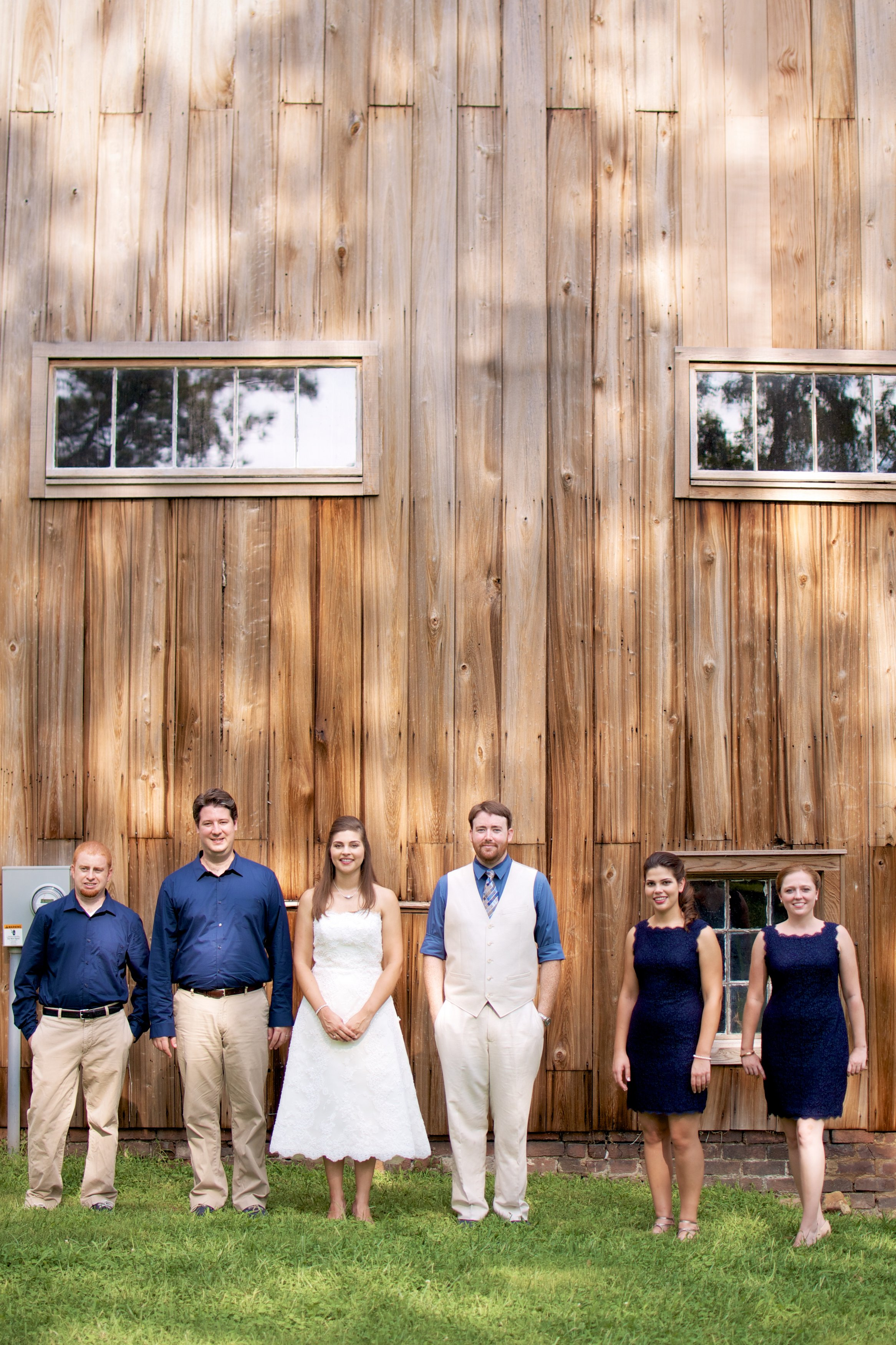 wedding party standing in front of rustic barn combsberry