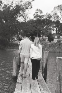 couple back to walking down pier holding hands oxford river