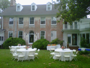 white linen tables and chairs on combsberry inn lawn for wedding reception