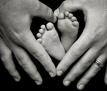 black and white photo of hands around baby feet
