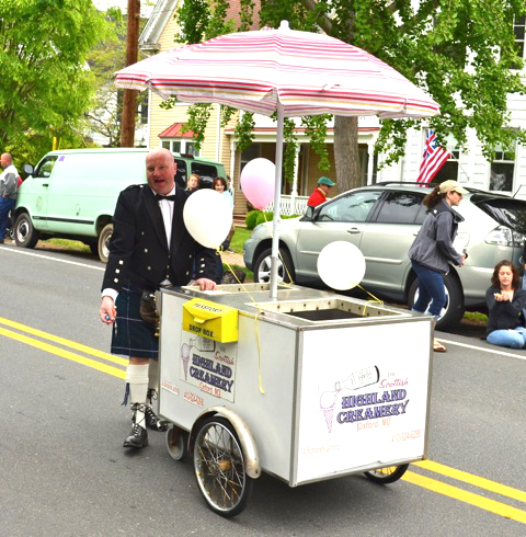 man in kilt uniform pushing ice cream cart down the street