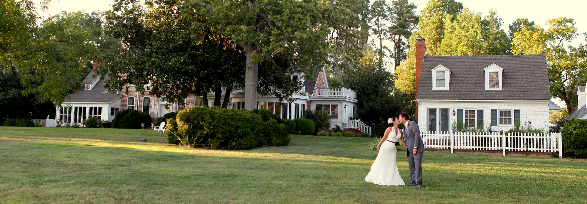 bride and groom kissing in front of combsberry inn main house and cottage