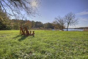 big yard with two adirondack chairs looking out to water
