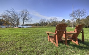 two adirondack chairs sitting in grass by waters edge