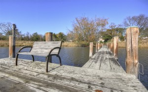 empty bench on dock by pier and water at combsberry inn