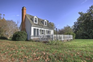 small gray house with picket fence deck