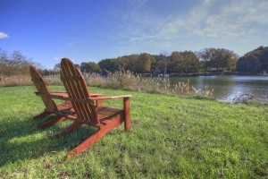 two empty adirondack chairs by water with houses in distance