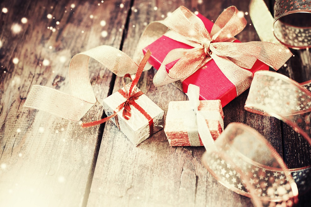 small holiday boxes with sparkle in photo on wood floor