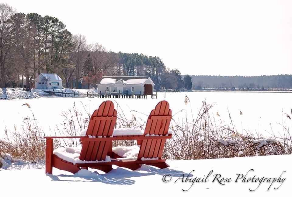 two empty red adirondack chairs with snow by snow covered water