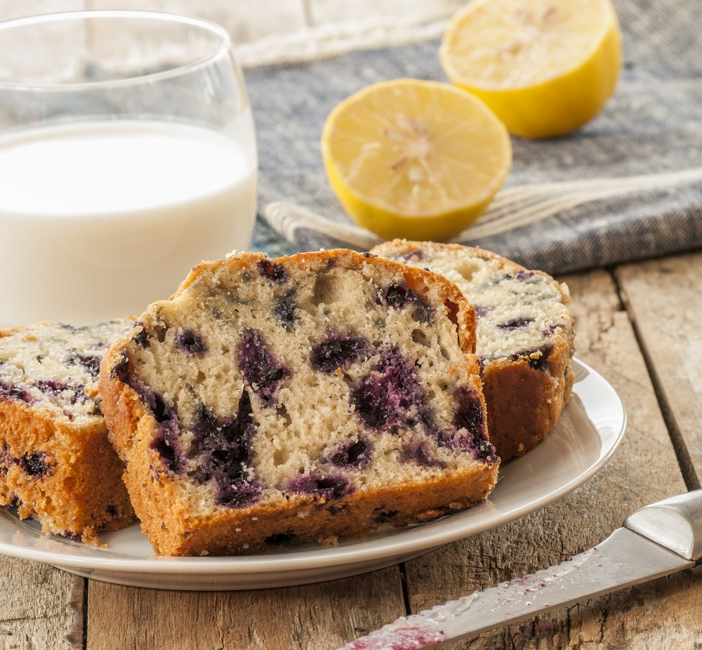 blueberry cake on plate next to lemons and glass of milk